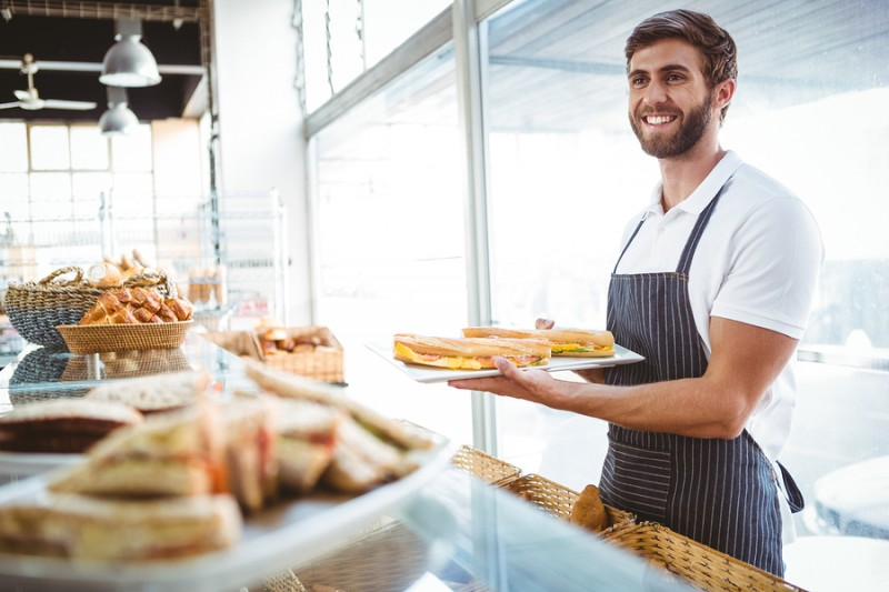 happy worker holding sandwiches at the backery